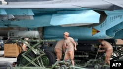 Russian servicemen attach a bomb on an SU-34 fighter jet before a mission from the Russian Hmeimim military base in Latakia Province, in the northwest of Syria.