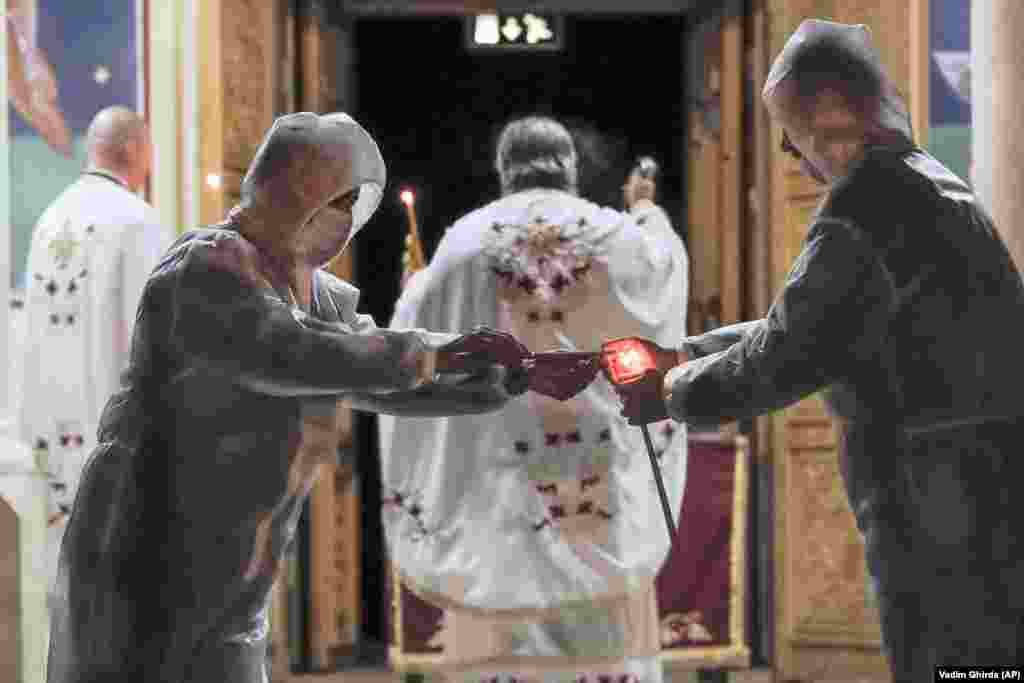 Volunteers wearing protective outfits light candles during the Orthodox Easter service in Bucharest on April 18.