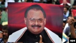 Supporters of Altaf Hussain, the leader of the Mutahida Qaumi Movement (MQM) political party hold his portraits as they gather in June 2014.