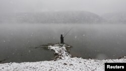 A man fishes during a heavy snowfall on the banks of the Yenisei River outside Krasnoyarsk, Russia. (Reuters/Ilya Naymushin)