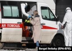 Медики в защитных костюмах сопровождают пациентку на госпитализацию. Москва, март 2020 года