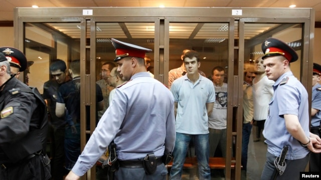 Defendants facing trial over clashes with the police during the Bolotnaya protests stand inside a glass-walled cage before a court hearing in Moscow on June 6.