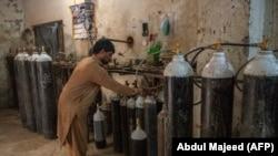 A worker fills oxygen cylinders for hospital use in Peshawar on December 7.