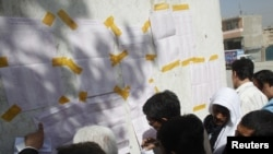 Representatives of Afghan candidates check vote results in front of a polling station in Kabul on September 19.