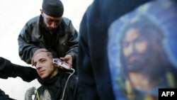 A Shi'a in Karbala has his head shaved alongside an image of Imam Hussein on the eve of Ashura.