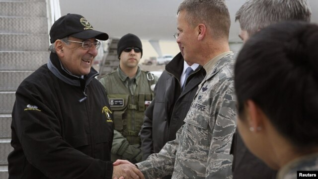 U.S. Defense Secretary Leon Panetta (left) is greeted by a serviceman as he arrives at the Manas Transit Center on March 13.