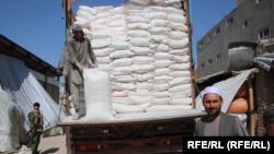 یک کارگر در حال پائین کردن بوری های آرد از یک موترباربری در شهر میمنه مرکز ولایت فاریاب