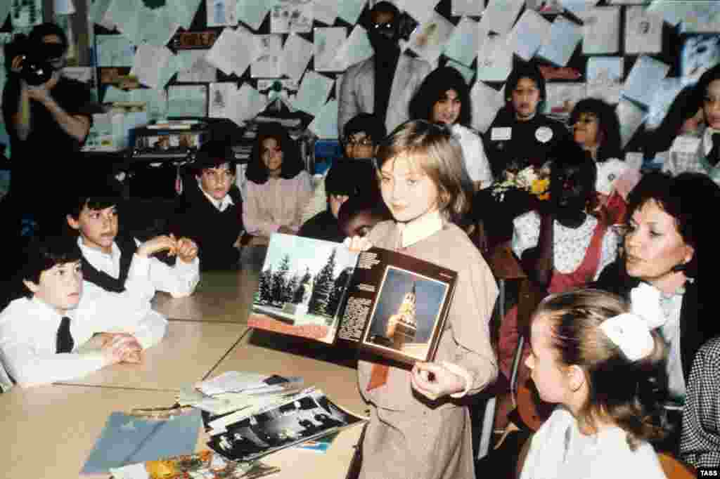Lycheva shows pictures of Russian landmarks to American schoolkids. Her U.S. tour followed the highly publicized visit of American schoolgirl Samantha Smith to the Soviet Union in 1983. Smith died in a plane crash in 1985, and Lycheva disappeared from public life. An attempt by Russian journalists to locate her in 2016 came up with nothing.