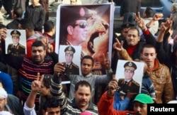 Прихильники військових мітингують із потретами Абдель-Фаттаха ас-Сісі перед пошкодженою будівлею суду, Імбаба під Каїром, 14 січня 2014 року