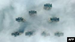 Верхушки небоскребов в Янчжоу почти скрыты сильным смогом.