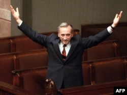 Then-Prime Minister Tadeusz Mazowiecki salutes deputies triumphantly from still-empty benches of the Polish parliament in Warsaw in September 1989.
