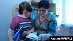 Ләйсирә Йосыпова (у) тәрбияче Алсу Гаффаровага яңа китаплар күрсәтә