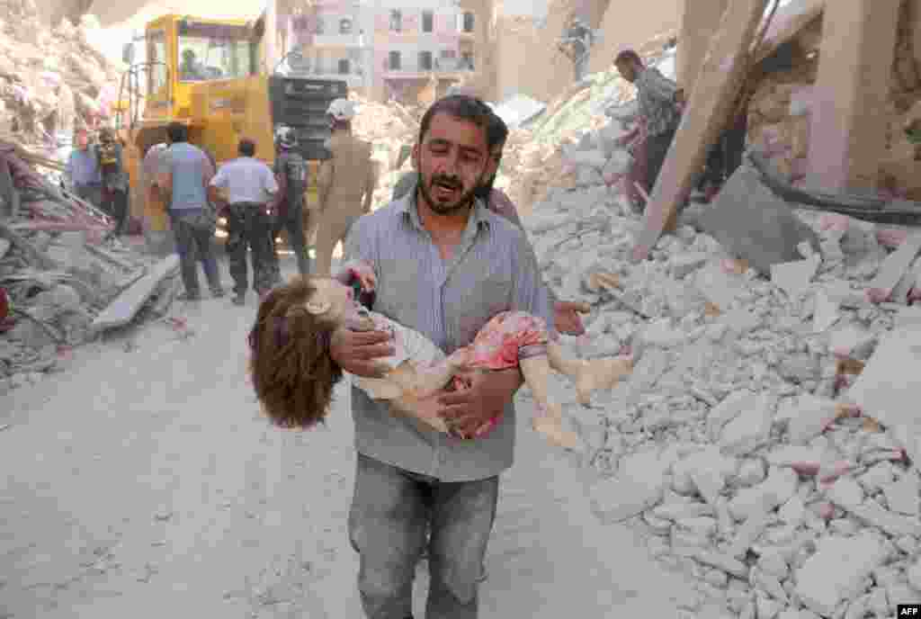 A Syrian man carries the body of a child following a reported air strike by Syrian government forces in the Tariq al-Bab neighborhood in the rebel-held area of the northern city of Aleppo. (AFP/Thaer Mohammed)