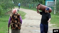 A Belarusian man carries a gas cylinder in the village of Krasnoe on June 22.