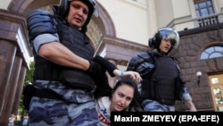Полиция задерживает протестующую в центре Москвы, 27 июля 2019 года