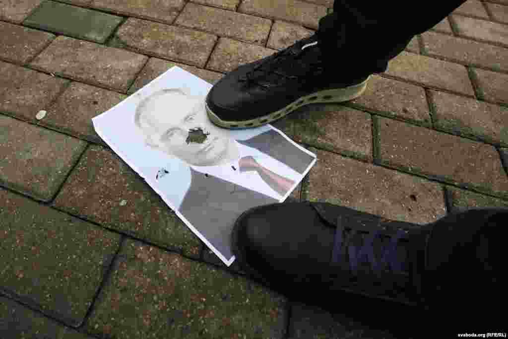 Протестующие в центре Минска бросают на землю и рвут портреты президента России Владимира Путина.