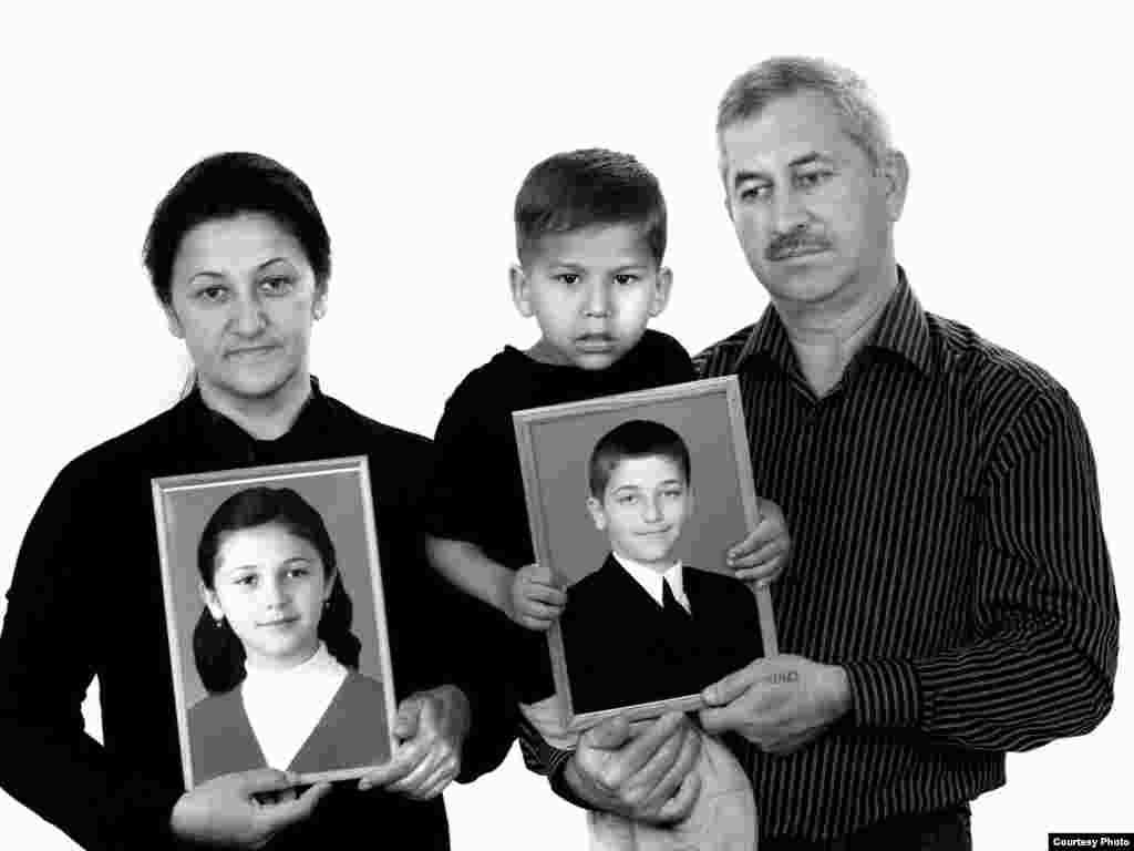"Elvira (left), Artur, and Georgy Tuayev, holding portraits of Karina (seventh grade) and Khetaga (fifth grade) - The family remembers Karina balking on the first day of school: ""I don't want to go! Let's go home!"" ""She had a premonition -- why didn't I listen to her?"" her grieving mother, Elvira, asks. She went with her two children to the first-day assembly. A three-day nightmare followed that ended with Elvira being carried out alive. Her children didn't survive. Three years later, Elvira was invited to the United States to talk about her ordeal. ""I thought, God, what am I going to talk about? There was a room full of people, a table full of food. I remember, I picked up a glass of water and looked at it, and it all just rushed out of me. 'Do you know what a drop of water is? What it tastes like? How much you can crave it? I sat and watched as people were dying in front of me, not eating, not drinking.' I told them everything -- how we sat, how thirsty we were, how we drank urine fr"