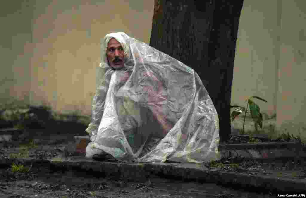 A Pakistani laborer looks on under plastic sheeting to keep dry from the rain in Islamabad. (AFP/Aamir Qureshi)