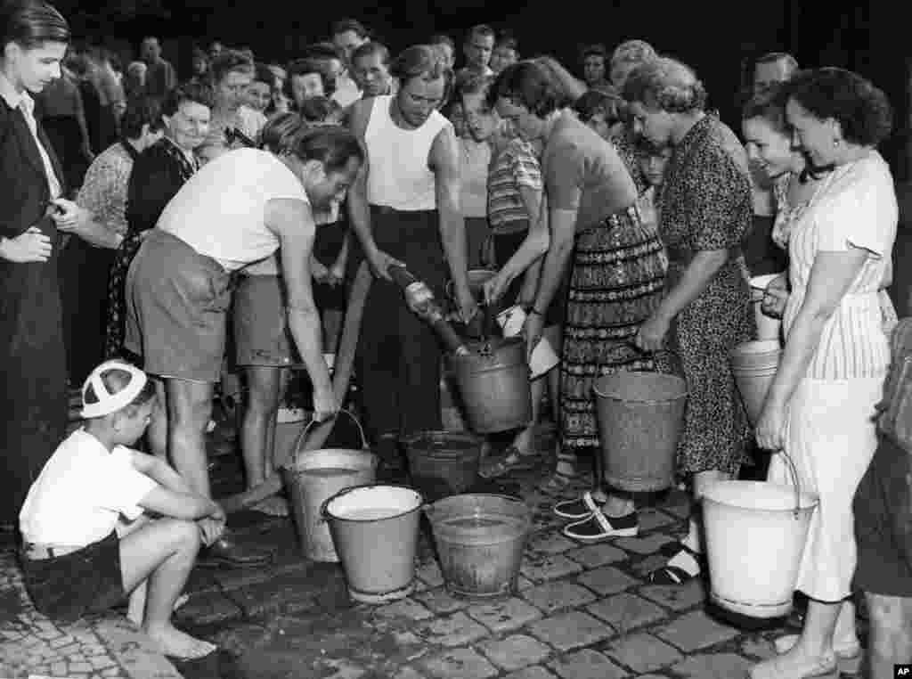 Жители Западного Берлина заполняют ведра водой из пожарного шланга, 3 июля 1948 года. После того как СССР перекрыл все поставки, люди вынуждены были часами стоять в очередях.