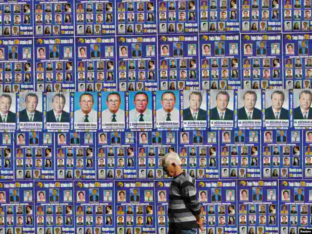 A man walks past a wall in central Sarajevo decorated with campaign posters ahead of Bosnia's October 3 parliamentary and presidential elections. Photo by Danilo Krstanovic for Reuters