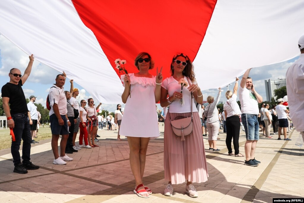 Die Leute trugen zwei riesige weiß-rot-weiße Flaggen ...