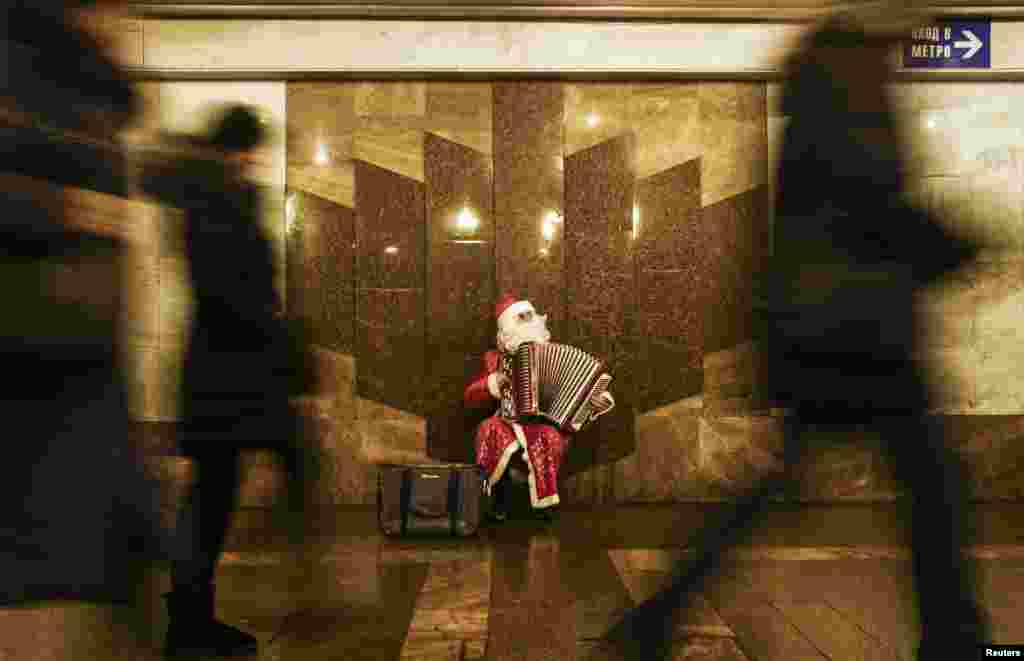 A man dressed as Father Frost, the Russian equivalent of Santa Claus, plays accordion at an underground crossing in Moscow. (Reuters/Maxim Shemetov)