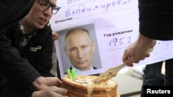 Орусия -- Оппозиция активисттери президент Путиндин сүрөтү чапталган пенсионердик карточканын алдында торт кесип жатат. Москва, 7-октябрь, 2012.