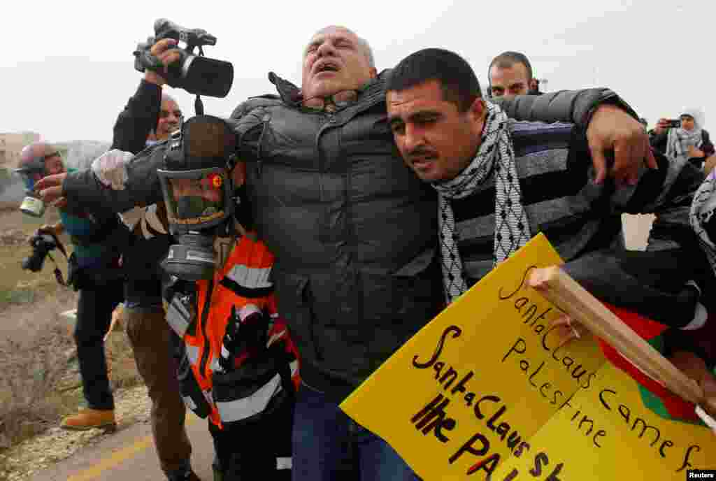 Betlehem, Günbatar kenardaky protest mahalynda ysraýyl goşunlarynyň pürken göz ýaşardyjy gazyndan essi aýylan palestin kameraçysynyň ewakuasiýa edilýän pursaty. 23-nji dekabr. (Mussa Qawasma/Reuters)