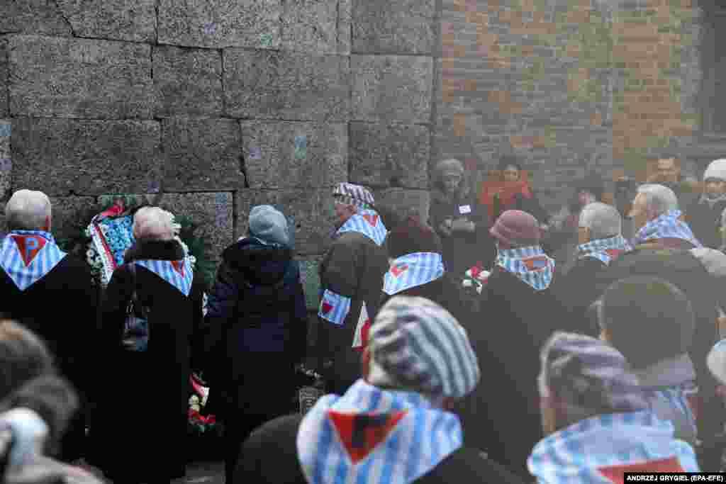 Бывшие узники лагеря возлагают венок к Стене смерти. Здесь расстреливали заключенных. Стена между двумя бараками, в которых было слышно все. 27 января 2020 года