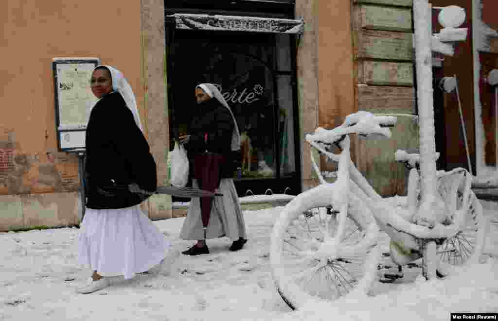 Nuns walk past a bike covered in snow during a heavy snowfall in Rome. (Reuters/Max Rossi)