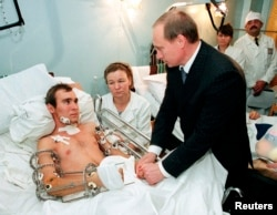 Then-Prime Minister Vladimir Putin speaks to a Russian soldier wounded in Chechnya at a military hospital outside Moscow on December 28, 1999.
