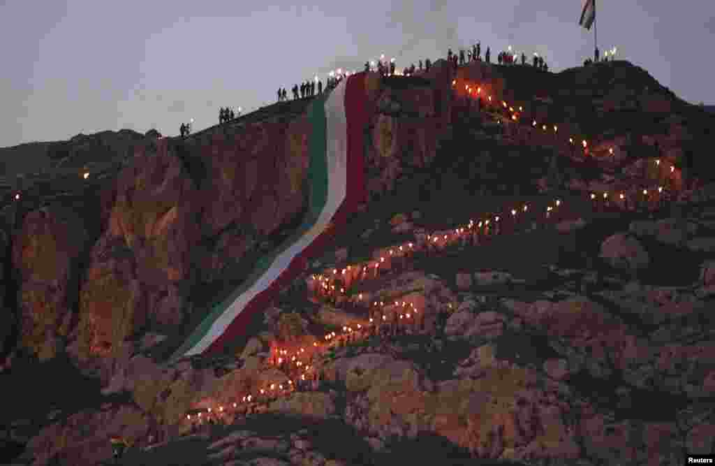 Iraqi Kurdish people carry torches up a mountain where a giant flag of Iraq's autonomous Kurdistan region is laid, as they celebrate Norouz Day, a festival marking their spring and new year, near Dahuk, on March 20. (Reuters/Azad Lashkari)