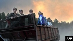 Volunteers ride on a trailer as they prepare to extinguish a fire at a forest near the village of Tokhushevo, some 50 kilometers outside Sarov.