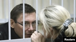 Former Interior Minister Yuriy Lutsenko talks with his wife, Irina, before the start of a court session in Kyiv on December 27.