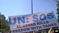 Antigovernment protesters carry a banner during a rally in the central Syrian city of Homs in early May.