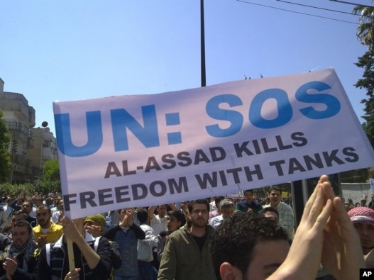 Antigovernment protesters carry a banner during a rally in the central Syrian city of Homs in early May. May 11, 201