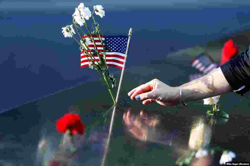 Një grua vendos lule dhe një flamur amerikan në memoralin për viktimat e 11 shtatorit në Nju Jork, teksa Shtetet e Bashkuara shënojnë 20-vjetorin e sulmeve terroriste.