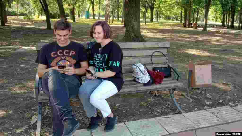 Un tânăr cu un tricou pe care scrie URSS și o tânără cu un tricou cu inscriptie în engleză pe o bancă într-un parc la Tiraspol