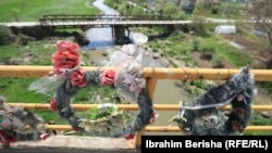 Kosovë: kurora lulesh të vendosura mbi urë në Lluzhan të Podujevës, në kujtim të viktimave që vdiqën në autobus nga një sulm i avionëve të NATO-s më 1999.