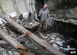 Жінка у зруйнованій внаслідок бойових дій будівлі, Слов'янськ, серпень 2014 року