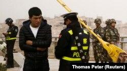 Кытай полициясы Шинжаңда жарандын документин текшерип жатат. 24-март, 2017-жыл.
