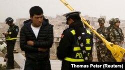 Көшеде жүрген адамның құжатын тексеріп тұрған полицей мен төңіректі бақылап тұрған қауіпсіздік қызметкерлері. Қашғар, Шыңжаң, Қытай. 24 наурыз 2017 жыл. Көрнекі сурет.