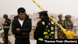 Сотрудники служб безопасности Китая проверяют документы. Кашгар, 24 марта 2017 года.