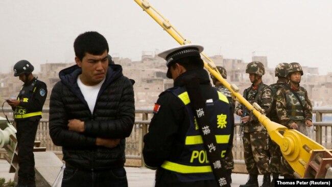 Сотрудник полиции проверяет документы на улице в городе Кашгар в Синьцзяне. 24 марта 2017 года.