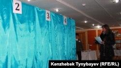 Женщина идет к кабинкам на одном из избирательных участков в Алматы, 15 января 2012 года.