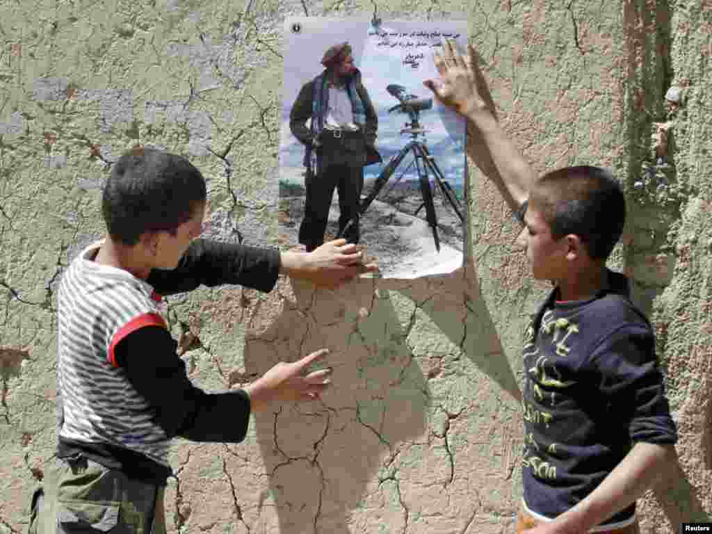 Afghan boys paste a poster of national hero Ahmad Shah Masud on a wall in the northern Panjshir Province on September 7. (Photo by Mohammad Ismail for Reuters)
