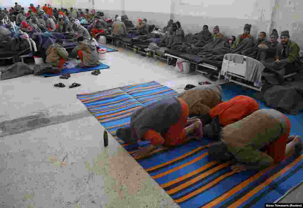 Suspects pray inside a hospital in the Hasaka prison.