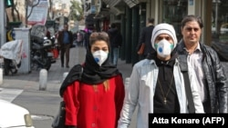 People wearing protective masks walk along a street in the Iranian capital, Tehran, on February 24.