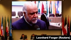 Russian Energy Minister Alexander Novak and UAE's Oil Minister Suhail Mohamed Al Mazrouei and OPEC Secretary General Mohammad Barkindo attend a meeting as Iran's Oil Minister Bijan Zanganeh is seen on a video screen in the OPEC headquarters in Vienna. December 2018