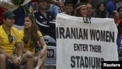 "An Iranian activist, Darya Safai holds a banner reading ""Let Iranian women enter their stadiums"" at the Iranian men's volleyball match against Egypt in the 2016 Olympics."